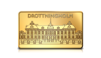 guldtacka med motiv av Drottningholm i 99,9 % guld. Guldtackan väger 5 gram och har en storlek av 24 x 14 mm